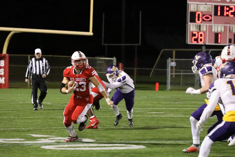 Joe Marinaro runs with the ball after breaking defender's tackles.