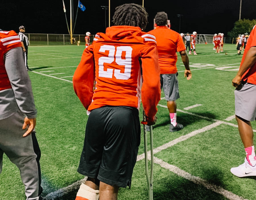 Isaiah Smith stands on the sideline of a football game
