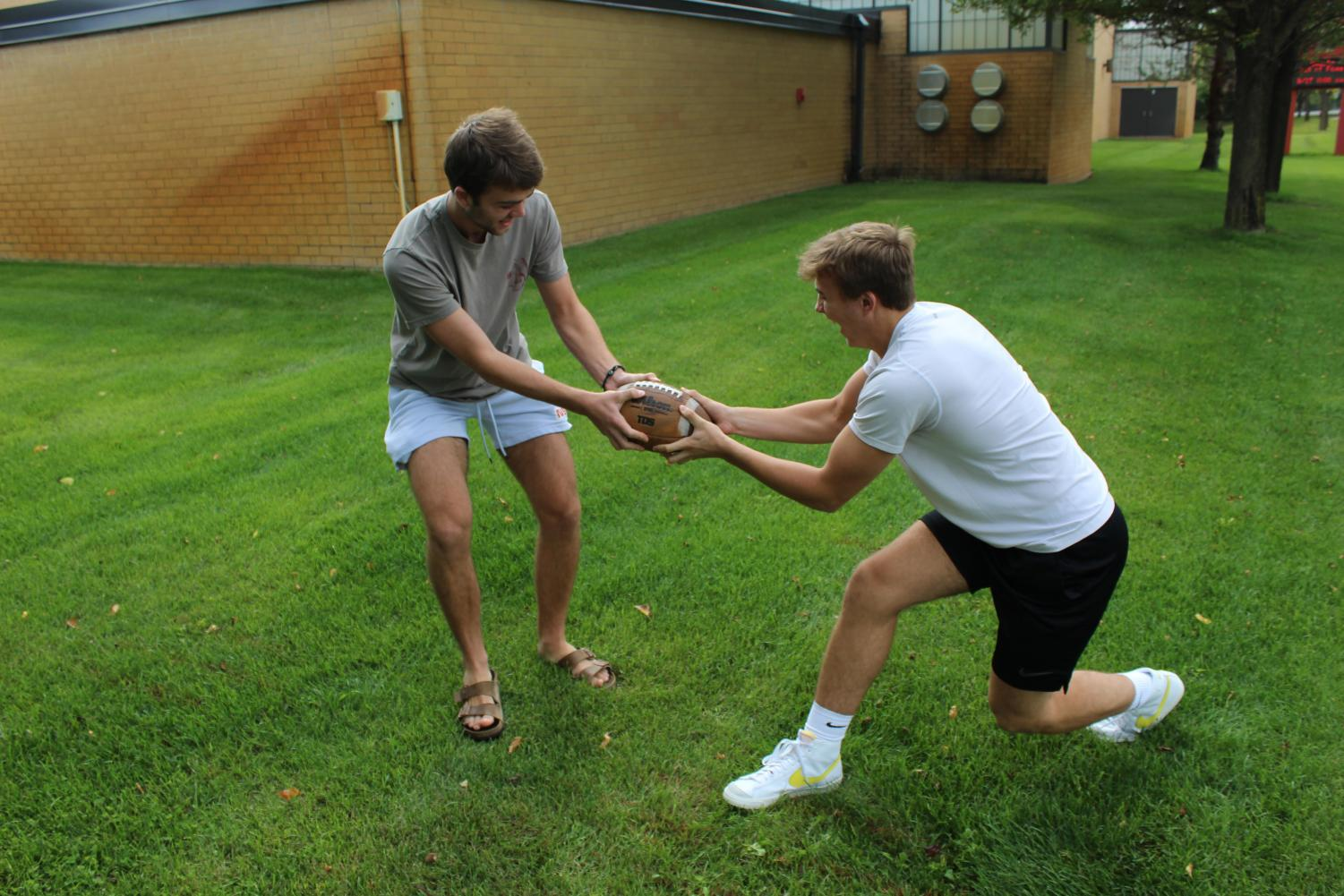 Seniors Matthew Nachbor and Zach Carden, who have differing opinions on the value of fantasy sports,  battle over a football.