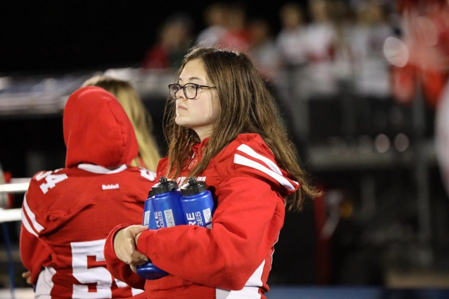 Senior Manager Kate Sawyer holds water bottles for the team on the sidelines.