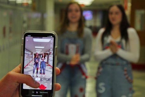 Seniors Elizabeth Valley and Sydney Wilharm make a TikTok in the hallways of BSM.