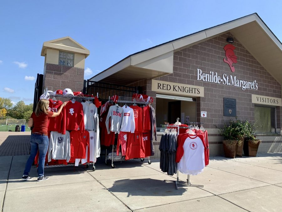A BSM Spirt Shop volunteer hangs merchandise in the shop's new location outside the stadium.