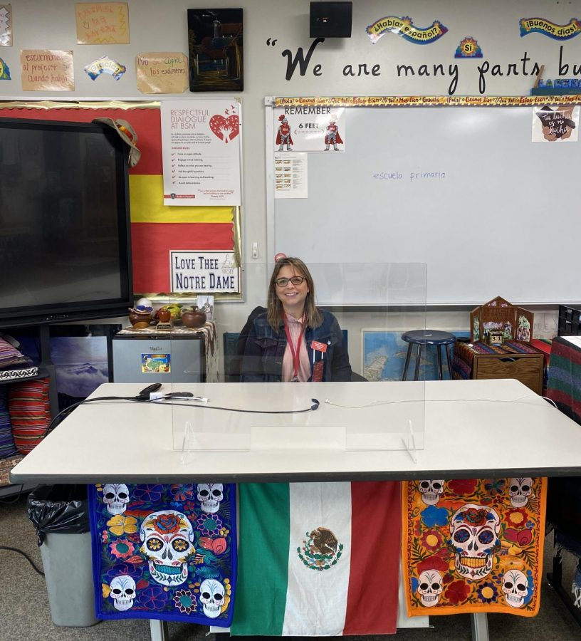 Señora Bernice Nava sits at her desk surrounded by various cultural items related to her home country of Mexico.
