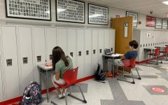 Freshmen Allison Cachat and Aiden Arndt listen to their teachers over Zoom while learning from a virtual learning space in the hall.