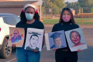 Seniors Maliah Jaiteh and Xela Gunvalson present signs picturing victims of police brutality.