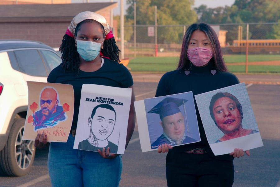 Seniors+Maliah+Jaiteh+and+Xela+Gunvalson+present+signs+picturing+victims+of+police+brutality.