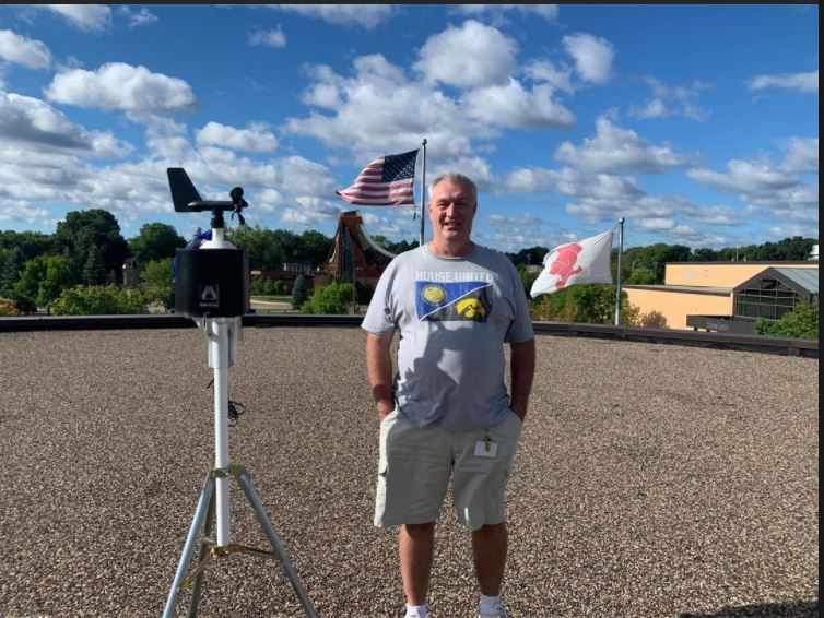 Mr. David Reynolds stands beside, the recently moved, weather station on the BSM roof.