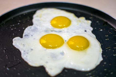 Three sunnyside up eggs sizzle waiting to be devoured by a person of culture.