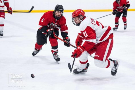 #21 Senior Asher Connolly fights for a puck
