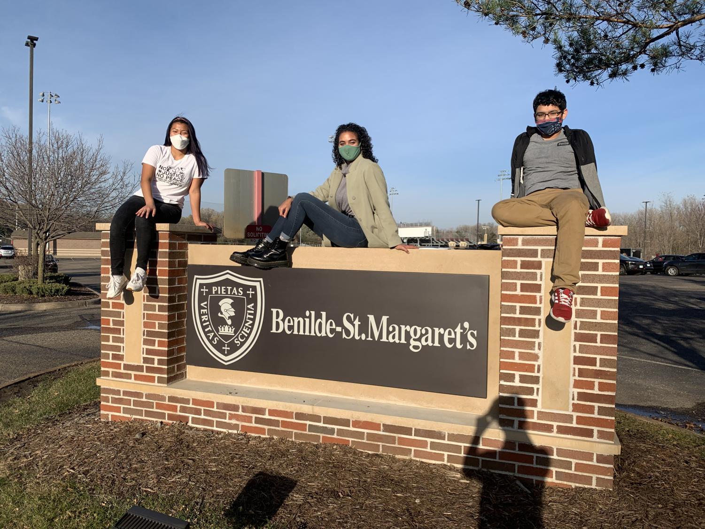 Seniors Xela Gunvalson, Sophie Coleman, and Johan Dominguez-Lopez sit atop the BSM sign.