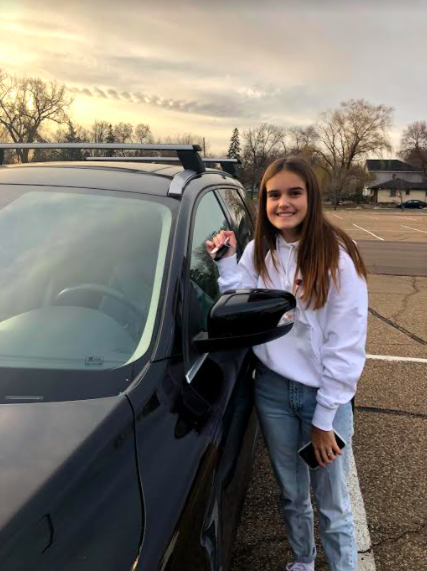 Sophomore Ella Kocourek poses with her car after driving to school.