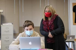 Señora Nava helps junior student Bennett Hilbrands in her Spanish 4 class.