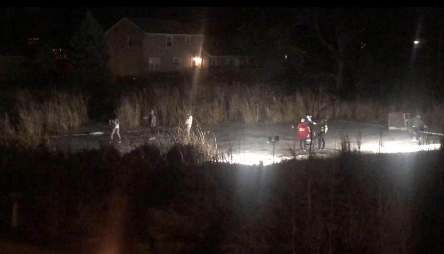 Drew and his friends safely socializing by playing pond hockey in his backyard.