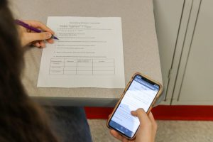 While taking a quiz, a student scrolls through their phone, looking for answers.