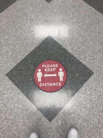 Signs remind students to keep their distance.