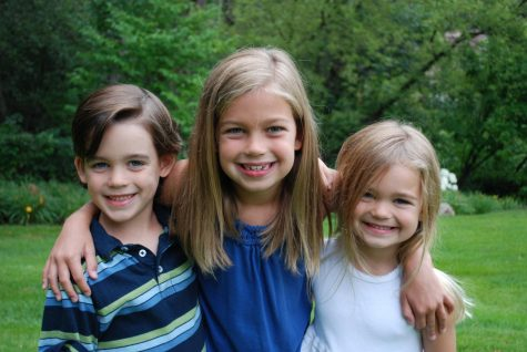 Charlie and his two sisters, Grace (middle) and Annie (right), smile nice and wide for a little family photo shoot.