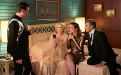 The Rose family gathers around Moira's phone in their final days in the Rosebud Motel. (Pop TV)