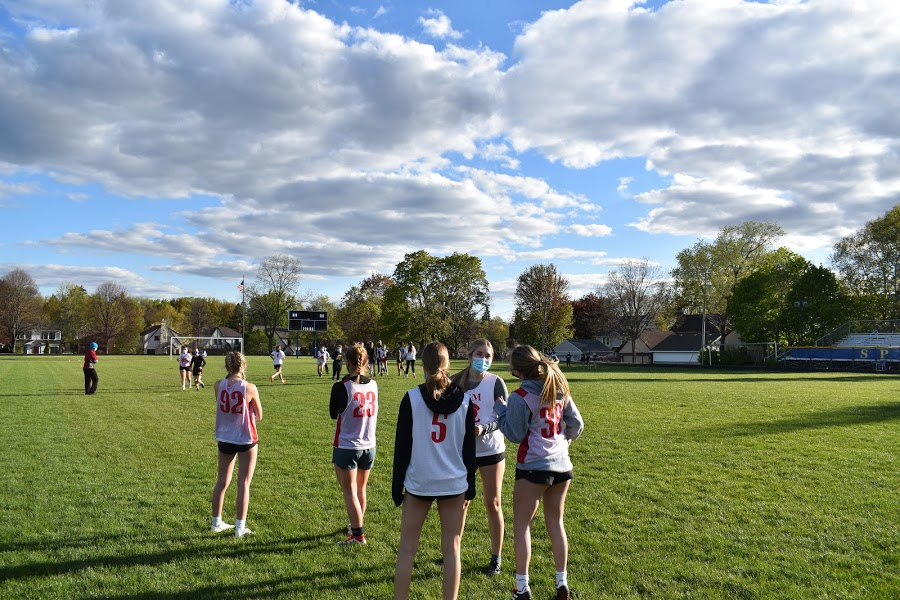 The girls' ultimate frisbee team cheers their team on.