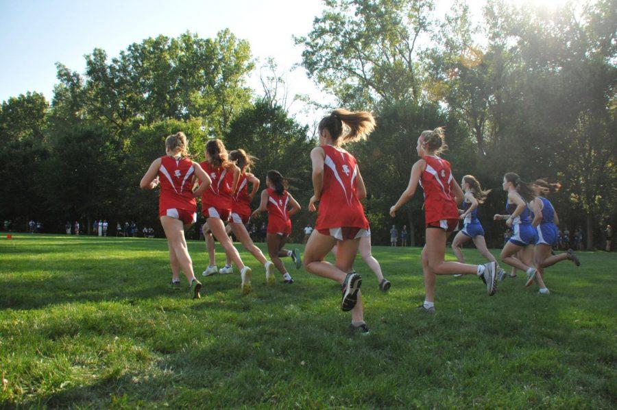 The girls varsity runners bolt off the starting line.