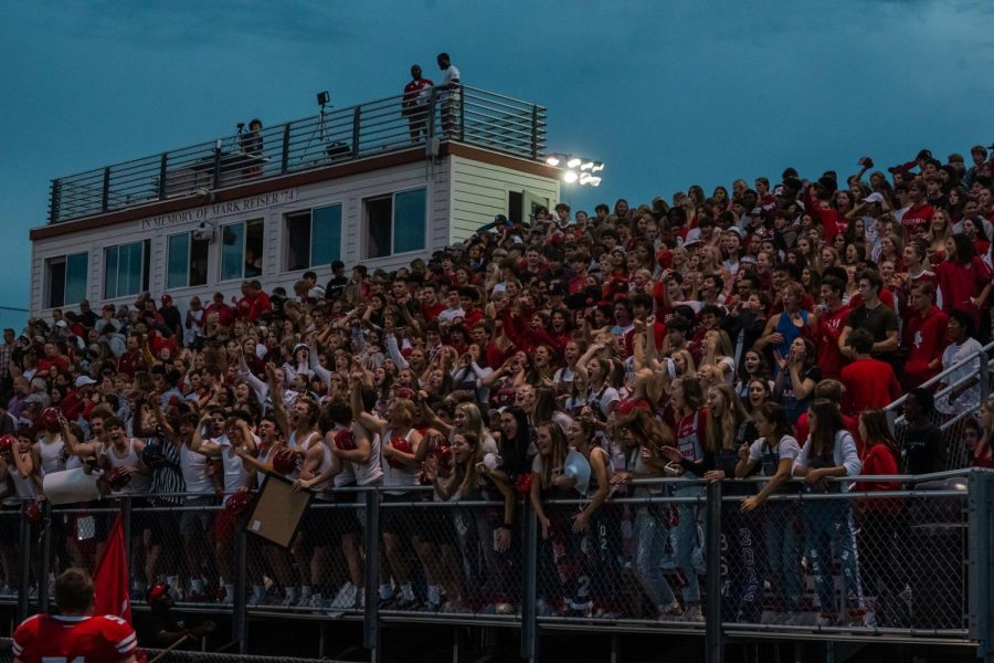 Students cheer at the football game the night before the homecoming dance.